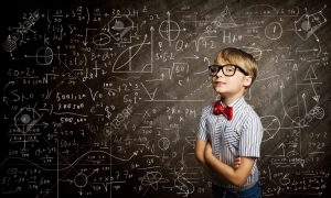 26179155-genius-boy-in-red-glasses-near-blackboard-with-formulas-stock-photo